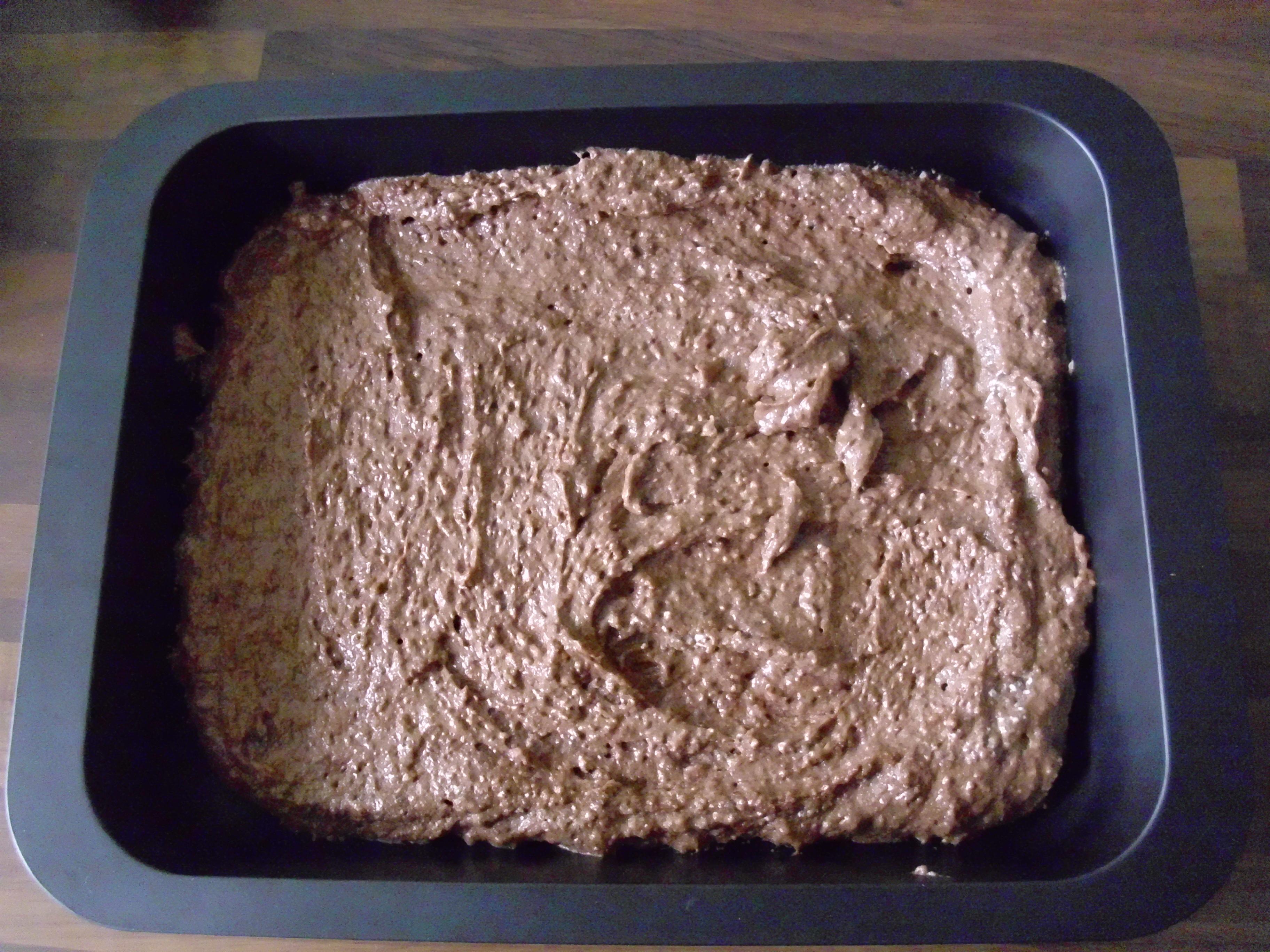 Der rohe Kuchenteig in einem teflonbeschichtetem Backblech, das etwa halb so groß wie der Ofen ist
